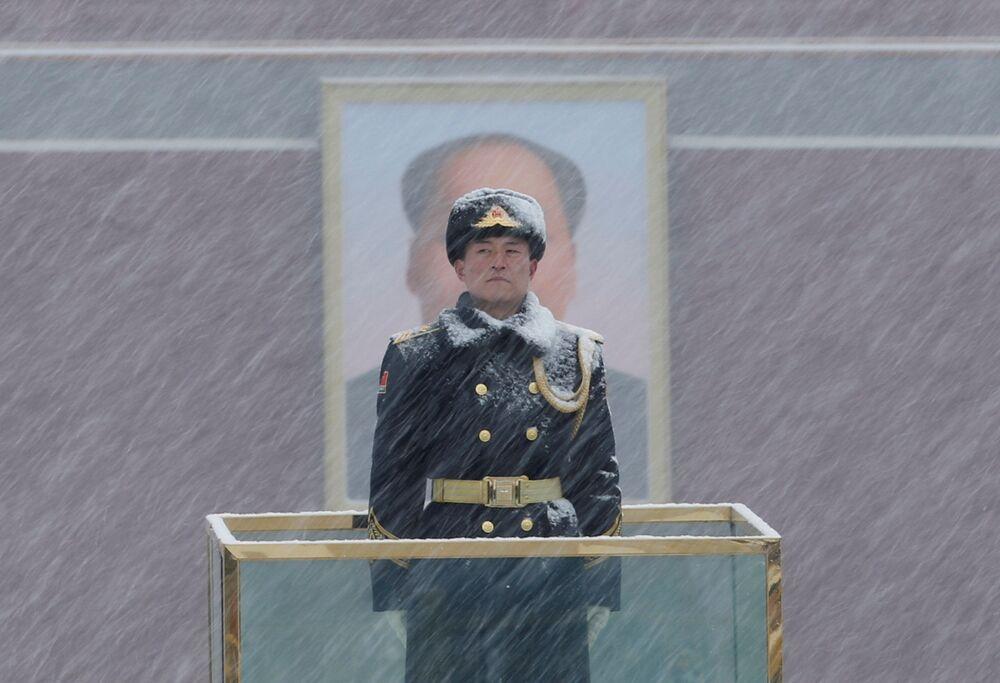 Soldado de guarda diante do retrato de Mao Tsé-Tung em meio a neve, em Pequim, China, 12 de fevereiro de 2019