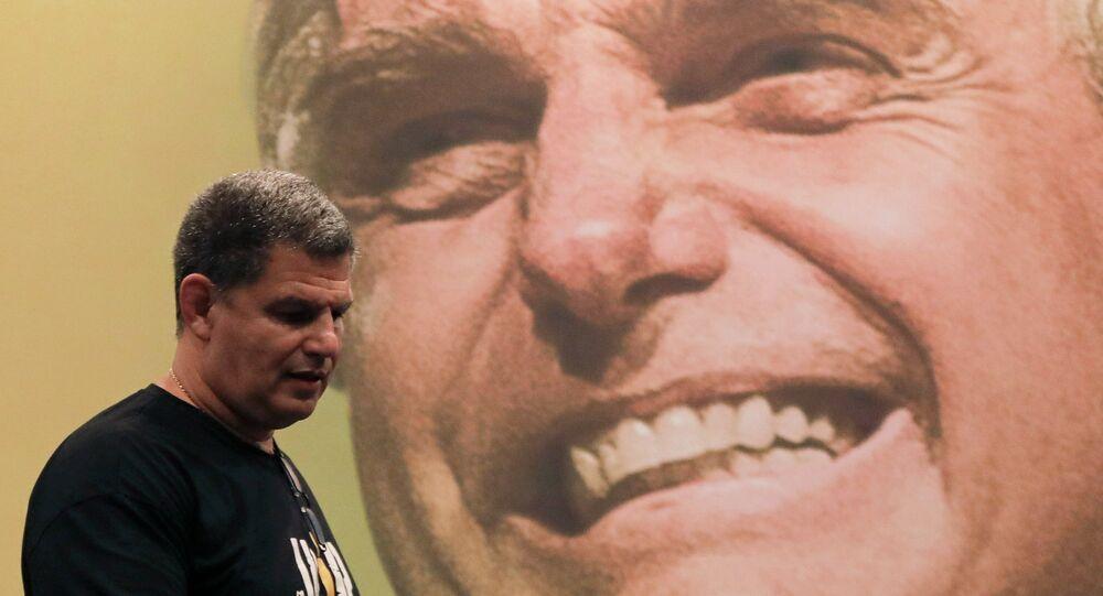 Gustavo Bebianno Rocha concede entrevista a jornalistas em hotel no Rio de Janeiro, com imagem do presidente do Brasil Jair Bolsonaro ao fundo, 7 de outubro de 2018