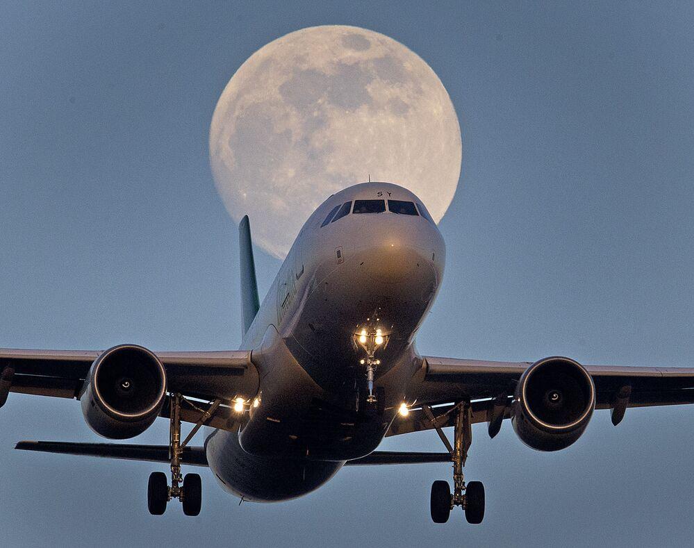 Aeronave aterrissa em aeroporto à medida que a lua sobe em Frankfurt, na Alemanha