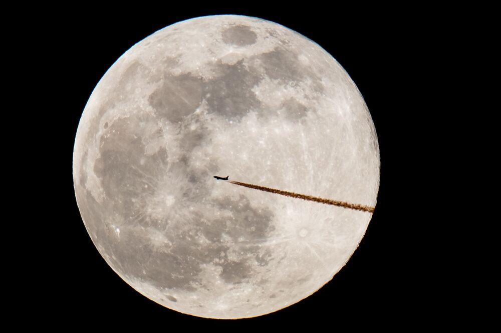 Um avião passa pela Lua cheia em Nuremberg