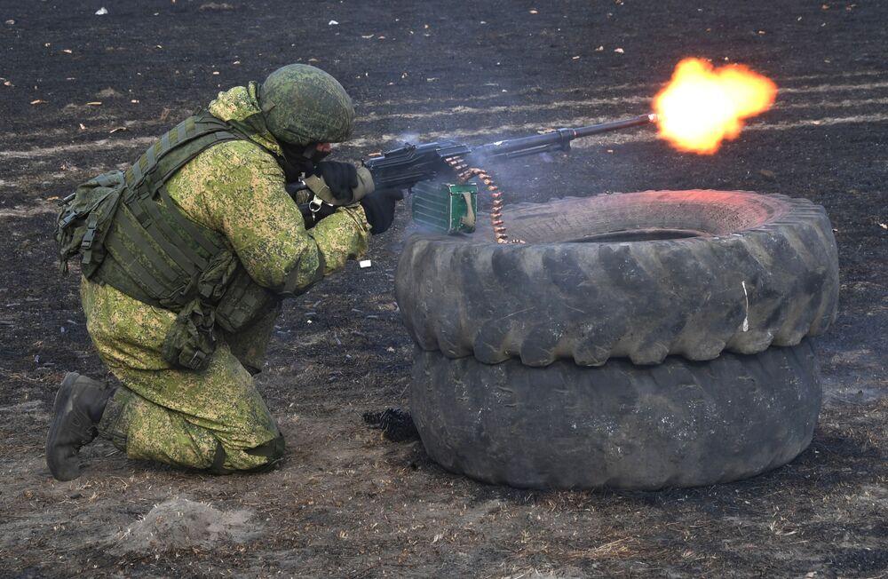 Soldado russo atira por trás de pneus empilhados durante exercício tático na região de Primorie, na Rússia