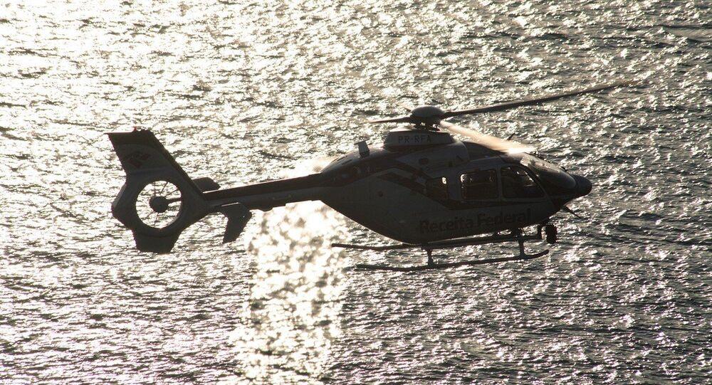 H135 fotografado sobrevoando o mar.
