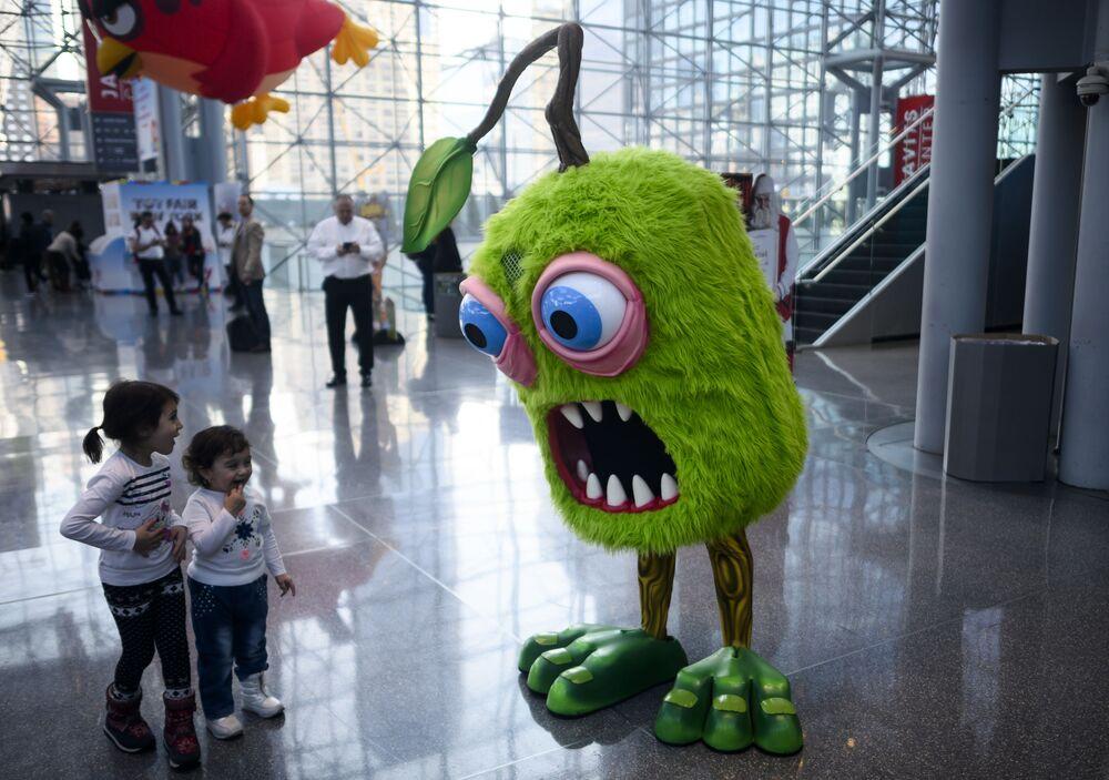 Crianças convivem com ator em fato de boneca na feira anual de brinquedos em Nova York