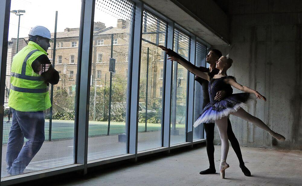 Um empregado observa os dançarinos na Escola Central de Balé em Londres