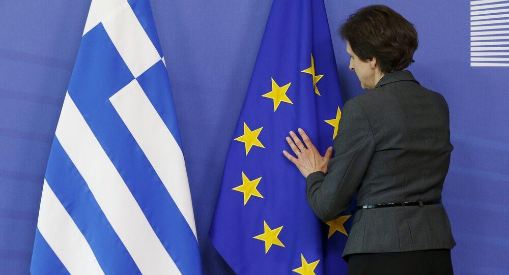 Funcionária arruma bandeiras da Grécia e da UE antes de encontro que aconteceu em Bruxelas entre o premiê grego Alexis Tsipras e o presidente da Comissão Europeia, Jean-Claude Juncker, em 3 de junho de 2015