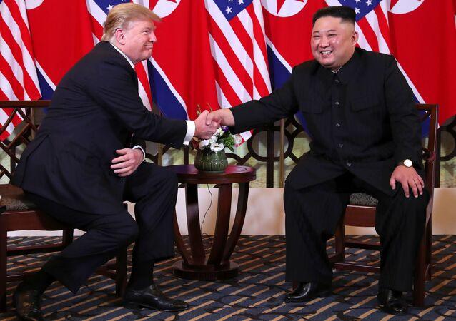 Donald Trump e Kim Jong Un apertam as mãos antes de reunião a portas fechadas durante cúpula em Hanói.