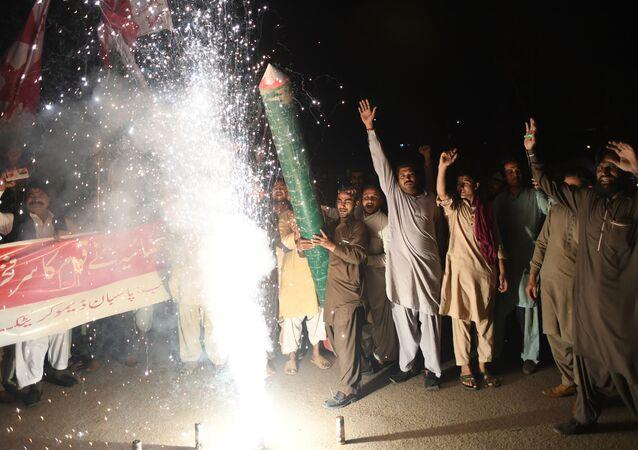 Apoiantes do Partido Democrático saúdam na capital paquistanesa de Carachi a derrubada pela Força Aérea do Paquistão de dois aviões indianos