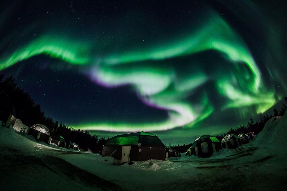 Brilhantes cores verdes iluminam o céu noturno no município de Rovaniemi, Finlândia