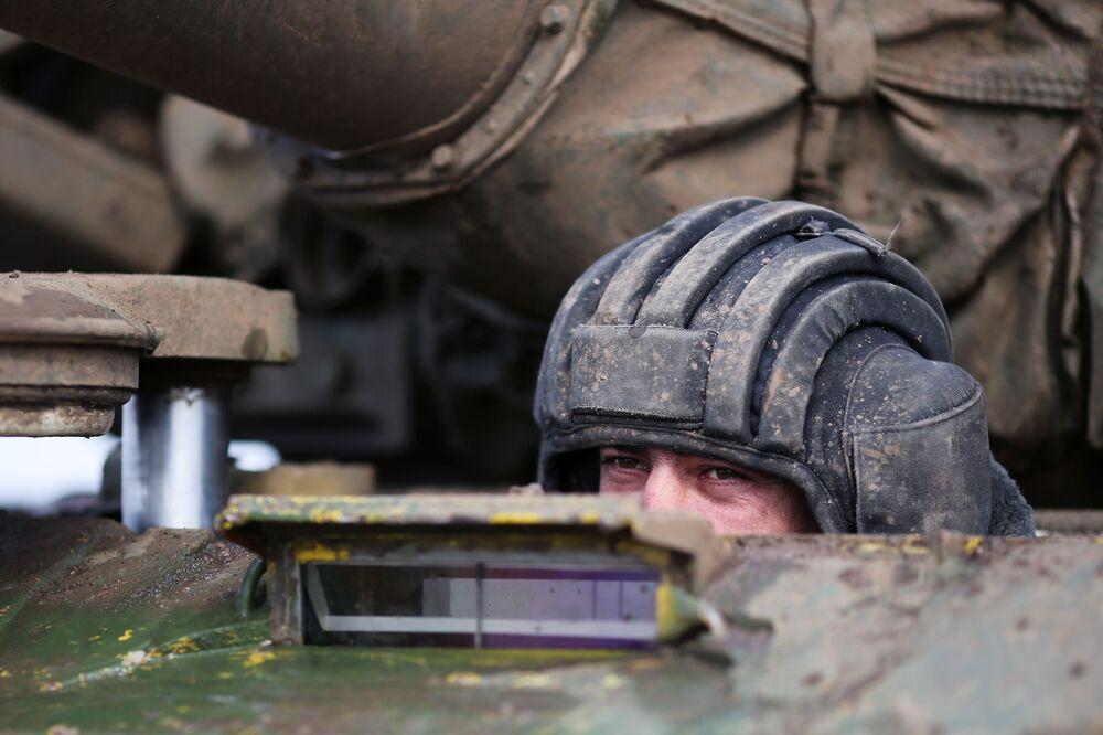 Um tripulante de uma equipe militar tentando chegar à vitória no biatlo de tanques
