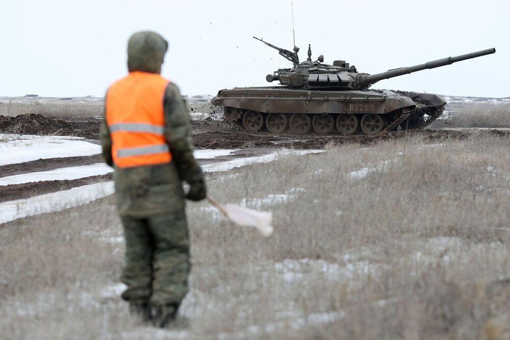 Militar observa um blindado passando perto no polígono de Prudboi, região de Volgogrado, durante a competição biatlo de tanques