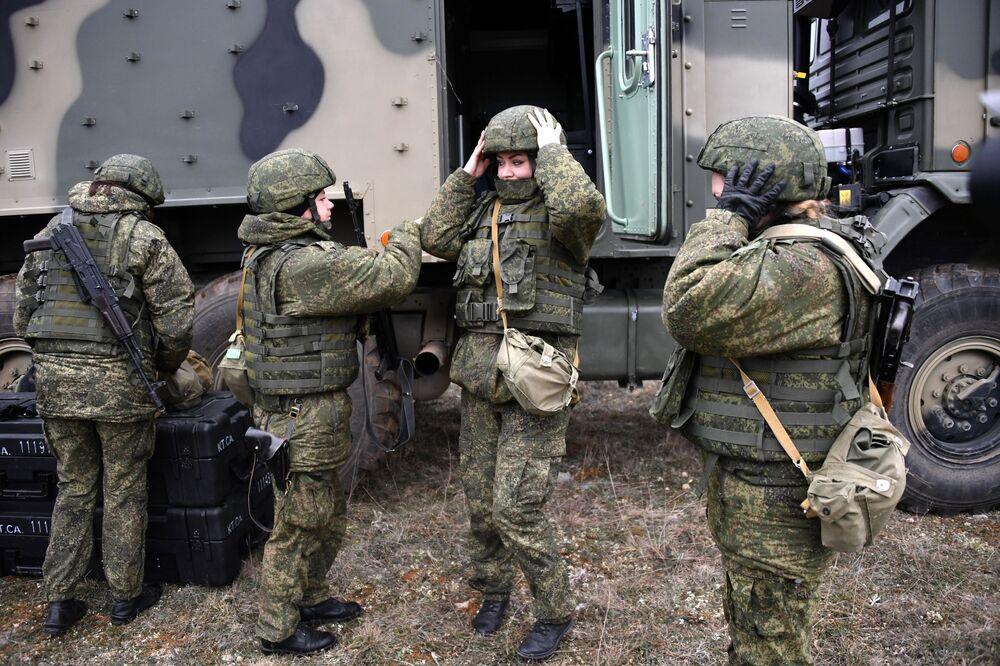 Militares da unidade feminina de pilotagem de veículos aéreos não tripulados da Brigada de Reconhecimento da Frota do Mar Negro perto de um posto de comando móvel do drone russo Orlan-10