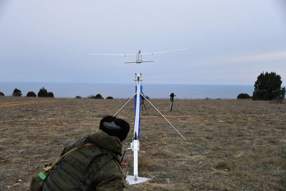 Uma engenheira técnica da unidade feminina de pilotagem de veículos aéreos não tripulados lança o drone de reconhecimento russo Orlan-10
