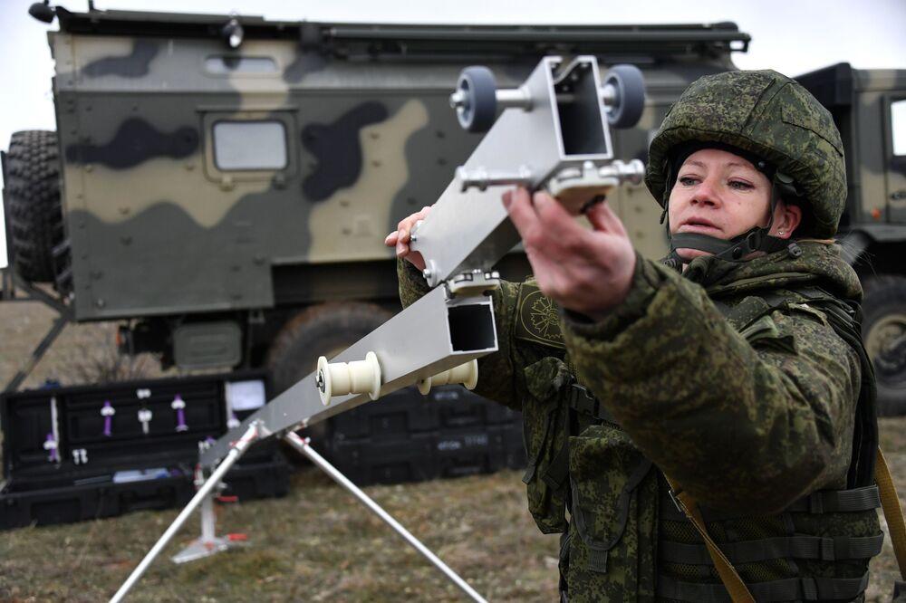 Uma engenheira técnica da unidade feminina de pilotagem de veículos aéreos não tripulados da Brigada de Reconhecimento da Frota do Mar Negro prepara a rampa de lançamento para o drone Orlan-10