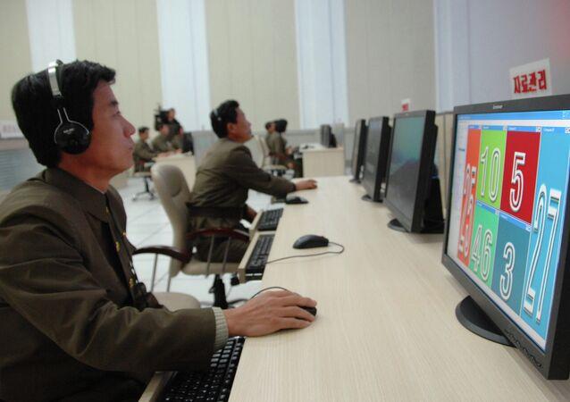 Cientistas e técnicos trabalham em seus computadores para controlar o lançamento do foguete Unha-3 no Centro Geral de Controle e Comando de Satélite na Coreia do Norte.