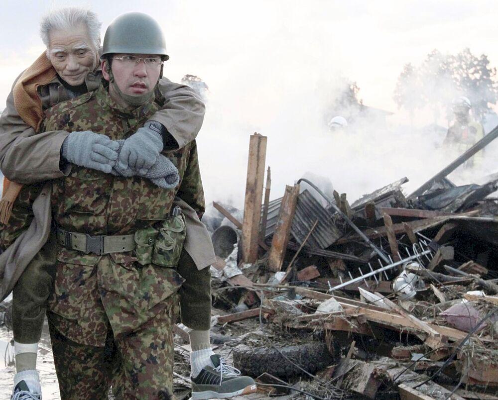 Soldado carrega vítima atingida por terremoto e tsunami na cidade de Natori, província de Miyagi, no Japão, 12 de março de 2011