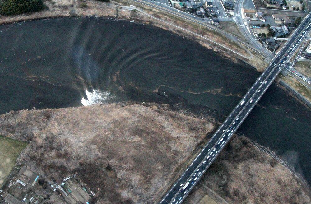 Foto aérea mostra ondas de tsunami movendo-se na cidade de Hitachinaka, na província japonesa de Ibaraki, 11 de março de 2011