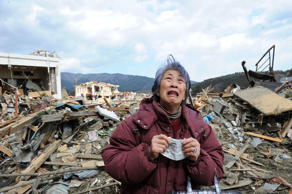 Idosa chora em frente a um prédio destruído na devastada cidade de Rikuzentakata, na província japonesa de Iwate, 19 de março de 2011