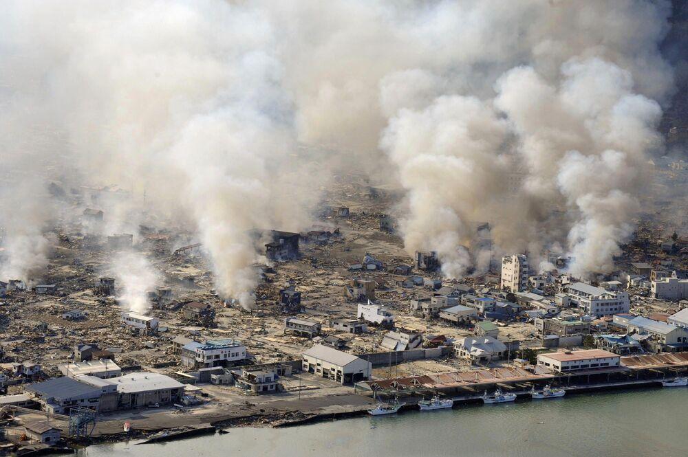 Fumaça densa se forma após tsunami que destruiu a cidade de Yamada, na província de Iwate, Japão, em 12 de março de 2011