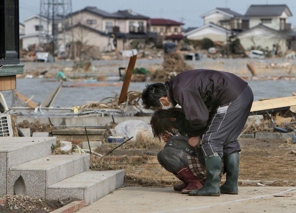 Pessoas chorando em frente a uma casa danificada na cidade de Watari, na província japonesa de Miyagi, 14 de março de 2011