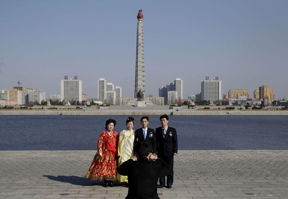 Uma família posa para foto de casamento em frente da Torre da Ideologia Juche, Pyongyang