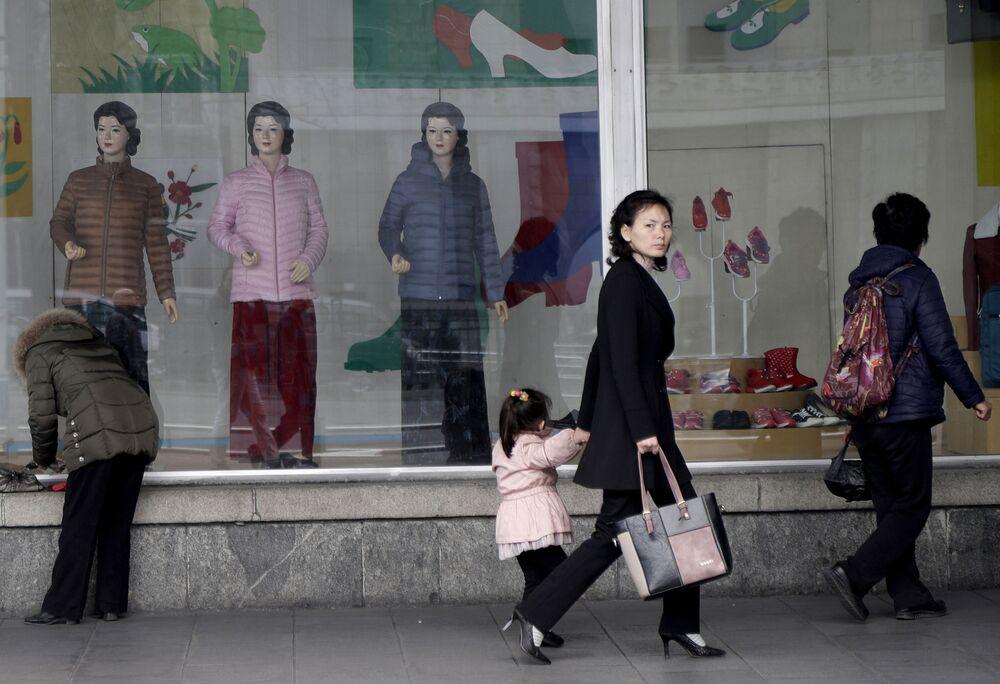 Norte-coreanas passam pela vitrina de uma loja no centro de Pyongyang