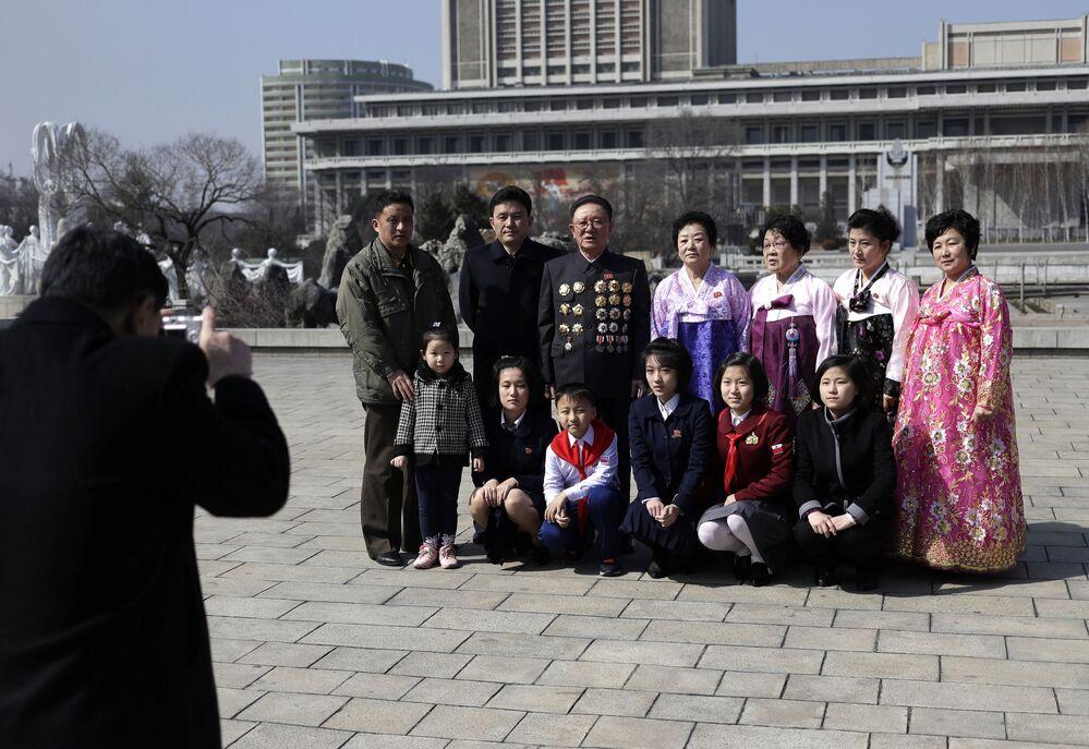 Diferentes gerações da mesma família são fotografadas no centro de Pyongyang durante o Dia Internacional da Mulher