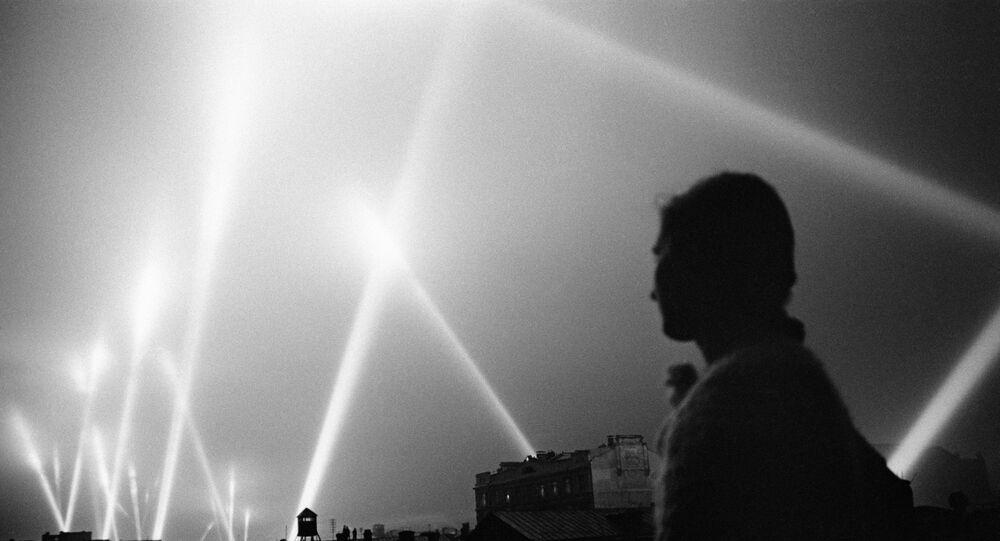 As luzes dos projetores das sistemas de defesa anti-aérea de Moscou iluminam o céu.