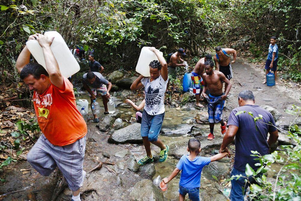 Pessoas enchem garrafas e outros recipientes com água do monte Ávila, nos arredores de Caracas