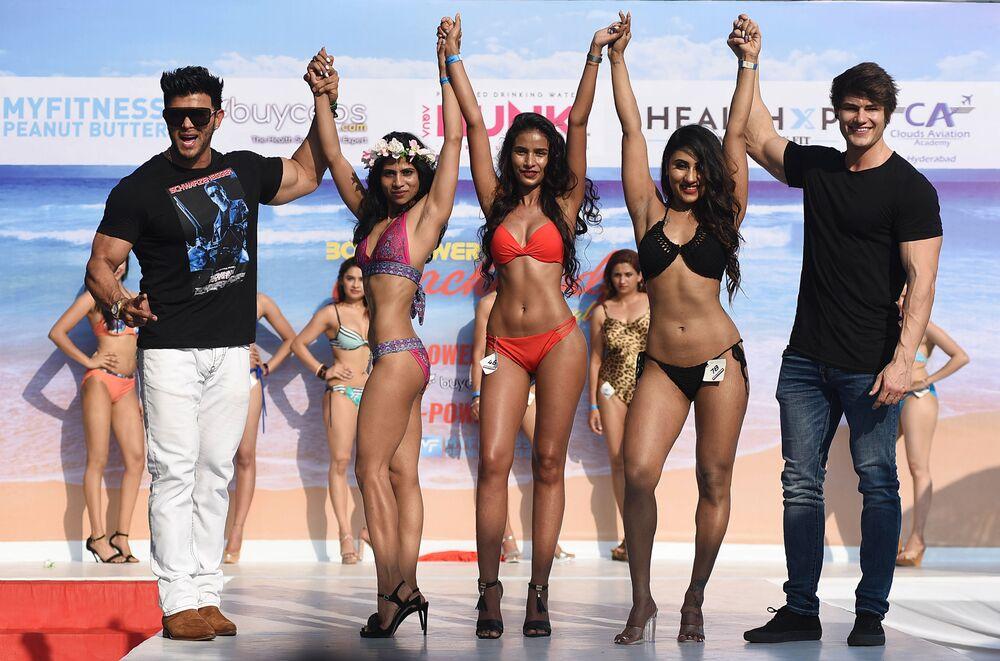 Ator e fisiculturista indiano Sahil Khan e fisiculturista e modelo fitness estadunidense Jeff Seid posam com participantes do Body Power Beach Show, o primeiro carnaval de corpos praieiros na Índia
