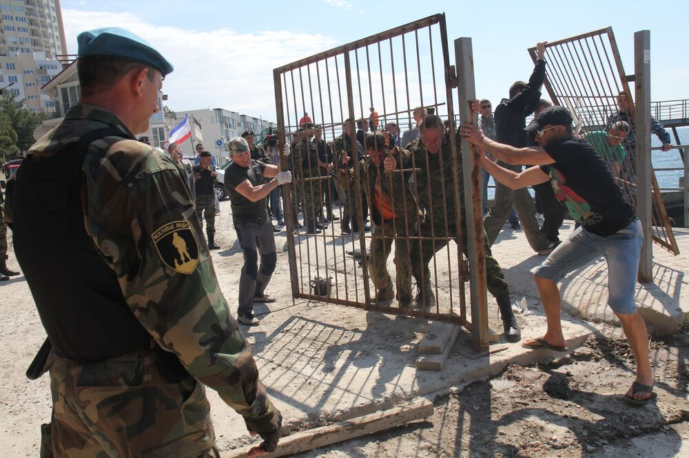 Voluntários retiram cercado na entrada de uma das praias perto da cidade de Yalta