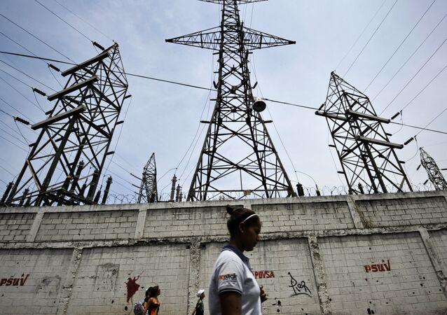 Uma mulher caminha em frente a postes de eletricidade em Caracas, Venezuela (Arquivo)