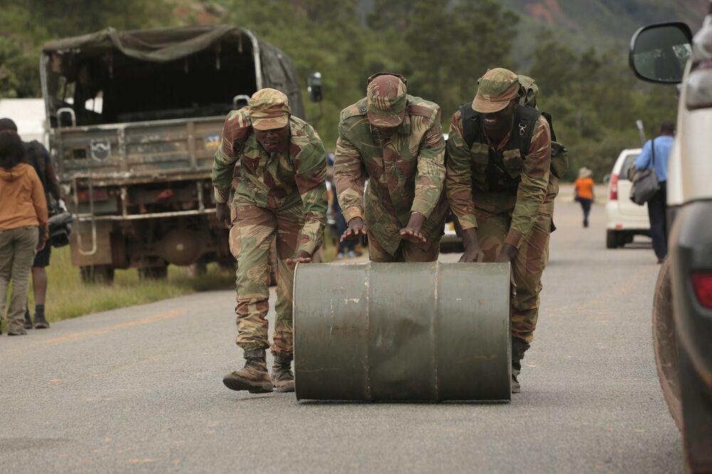 Soldados de Zimbabué empurram barril de combustível usado para operações de resgate na região de Chimanimani, Zimbabué