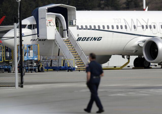 Um trabalhador caminha ao lado de um avião Boeing 737 MAX 8 estacionado.
