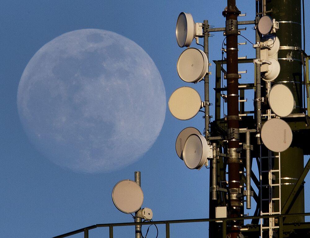 A Lua cheia se levantando por trás de uma torre de rádio no distrito alemão de Wachenbuchen, perto de Frankfurt