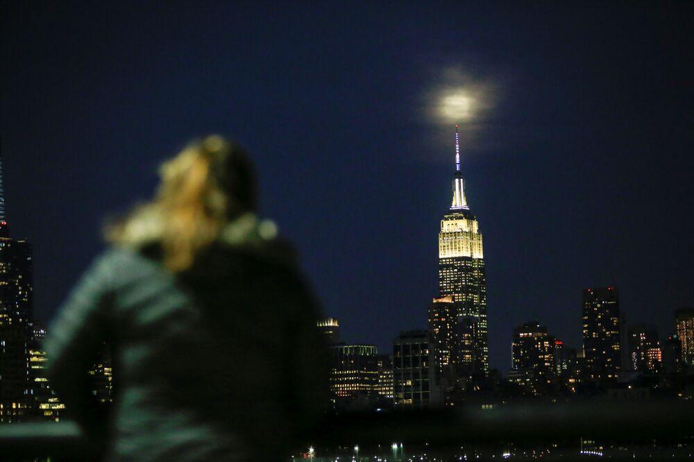 Superlua brilha por cima do arranha-céu americano Empire State Building, no centro de Manhattan, Nova York