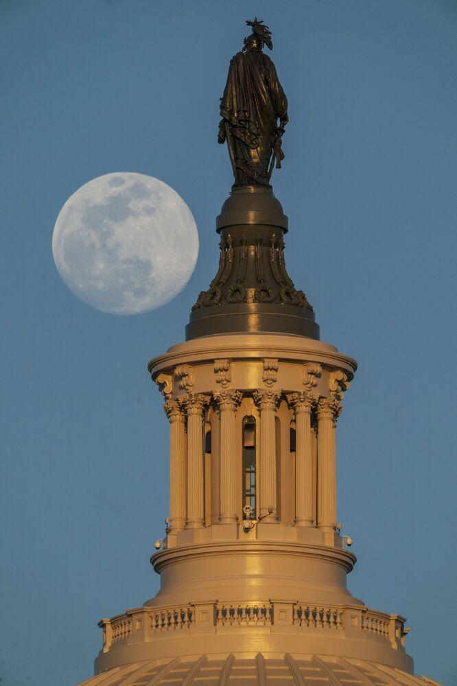 A Lua cheia captada à esquerda da Estátua da Liberdade, no cimo do Capitólio dos Estados Unidos, em Washington, D.C