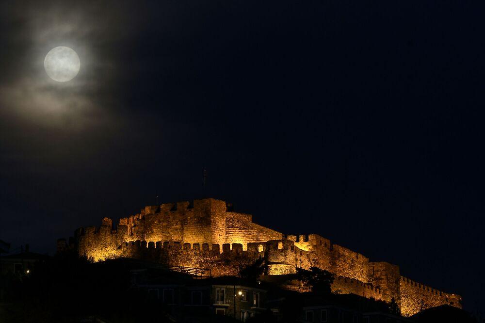 O Castelo de Molyvos iluminado pela Supelua entre nuvens no céu noturno, ilha de Lesbos, Grécia