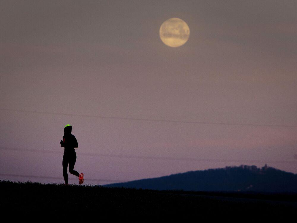 Uma jovem corre entre campos, antes de a Lua se pôr nos arredores de Frankfurt