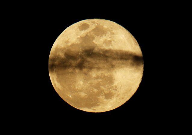 A Superlua se levanta entre as nuvens no céu noturno da Califórnia