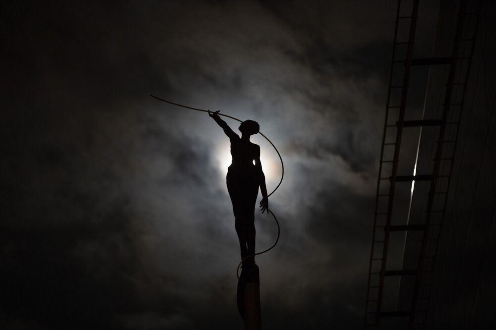 Silhueta de uma escultura iluminada pela Lua cheia, Bruxelas