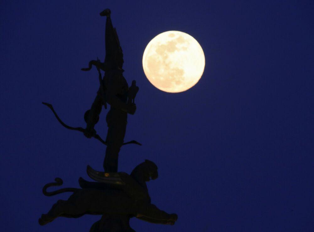 A Lua cheia se levantando por trás do Monumento da Independência em Almaty, Cazaquistão