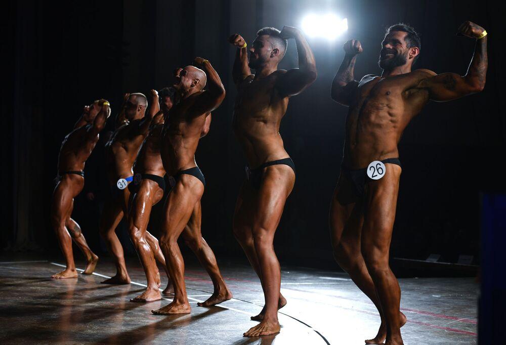 Homens marcam músculos dos braços no palco no campeonato aberto de fisiculturismo
