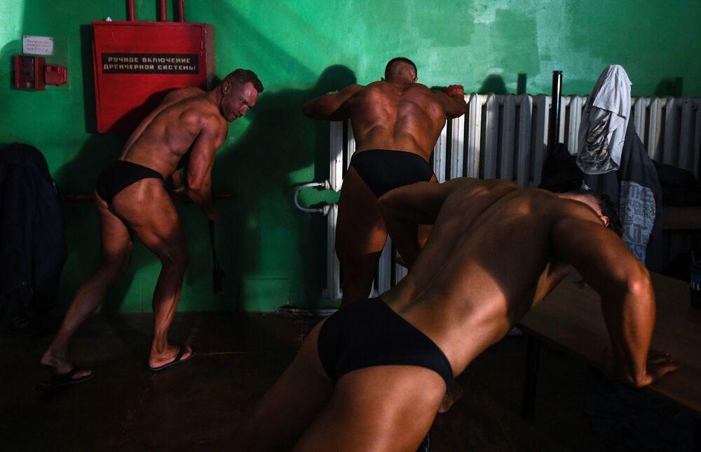 Homens fazem flexões antes de sair ao palco no campeonato aberto de fisiculturismo