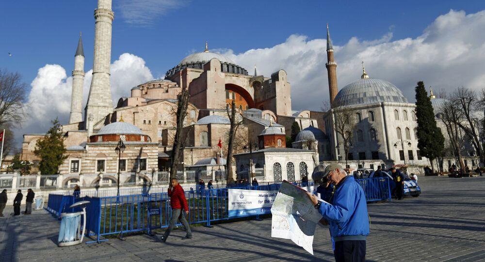A tourist couple checks a map, near the Byzantine-era monument of Hagia Sophia, at Sultanahmet square in Istanbul,Turkey January 14, 2016