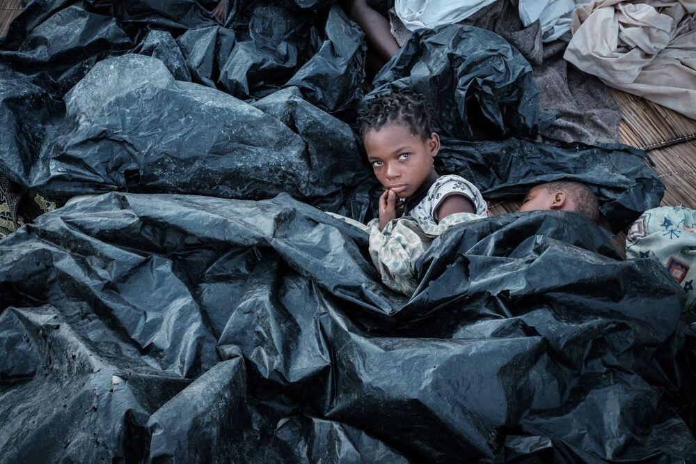 Duas irmãs, de 11 e 6 anos, se escondem em abrigo improvisado de plástico após o ciclone devastador que afetou Moçambique
