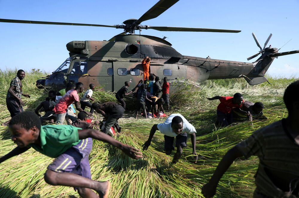 Moradores locais fogem da aterrissagem de um helicóptero da Força Nacional de Defesa da África do Sul que traz ajuda humanitária para um povoado afetado pelo ciclone, em Moçambique
