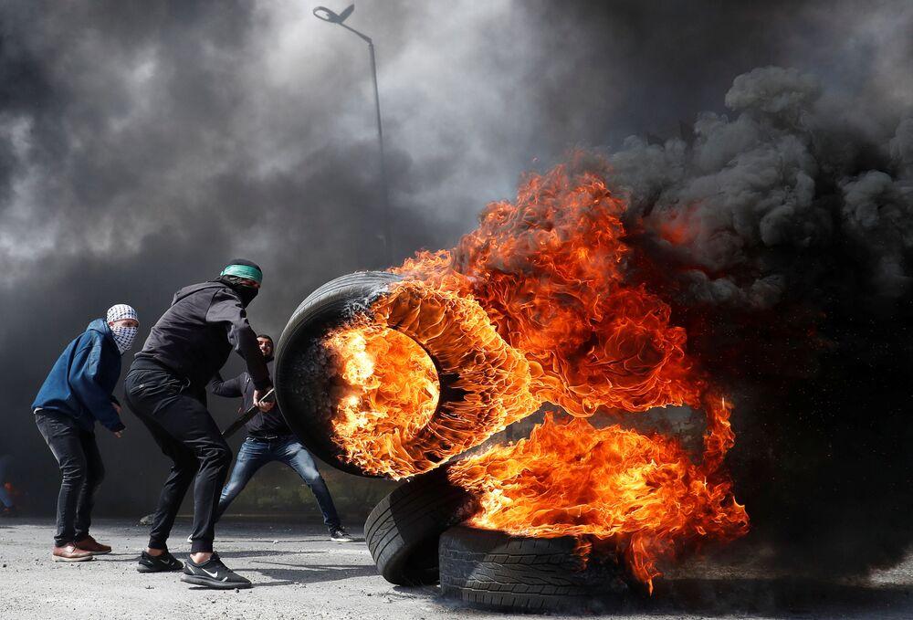 Manifestante palestino com pneu ardendo durante confrontos com tropas israelenses perto de povoação judia de Beit El, na Cisjordânia