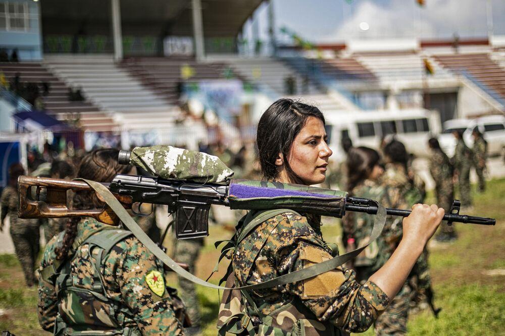 Jovens de um destacamento das Unidades de Proteção das Mulheres (YPJ) tomam parte no desfile militar dedicado à destruição total do Daesh (organização terrorista proibida em vários países, incluindo a Rússia), no leste da Síria