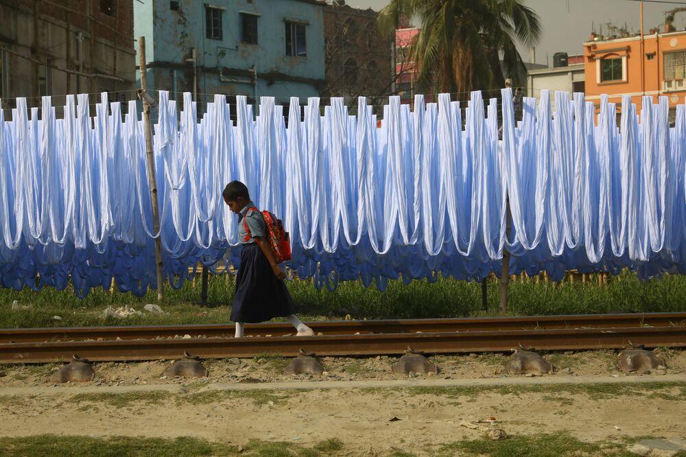 Aluna caminha pelos trilhos em Narayanganj, Bangladesh
