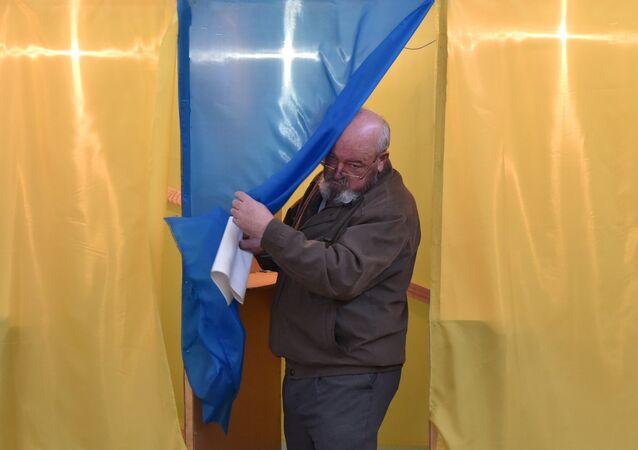 Eleitor é fotografado deixando uma cabine em zona de votação na cidade de Lviv, durante as eleições presidenciais na Ucrânia.